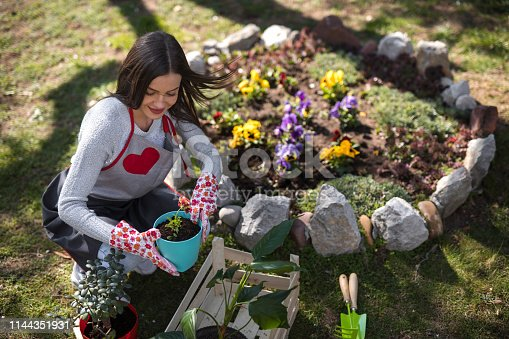 Happy young lady enjoys in gardening job