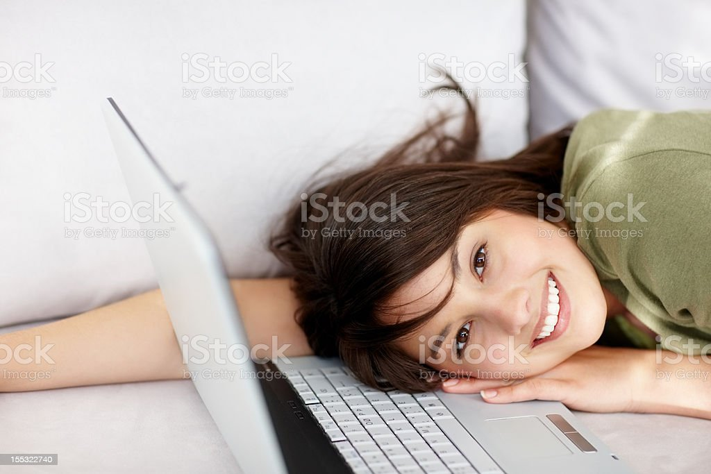 Happy young lady lying on couch with laptop royalty-free stock photo