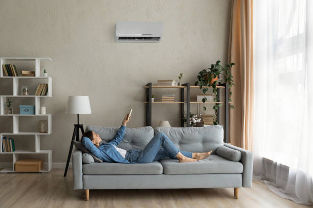 Happy young lady regulate climate at home using ac device stock photo