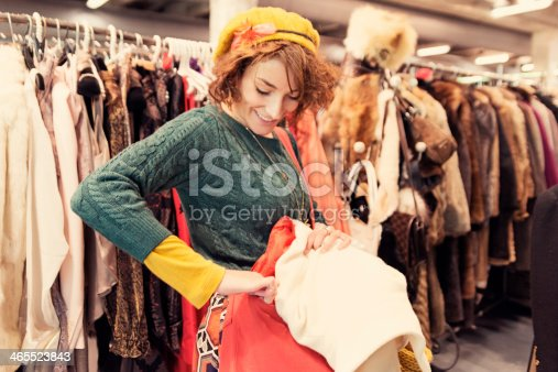 Young woman shopping in thrift market of vintage clothes.