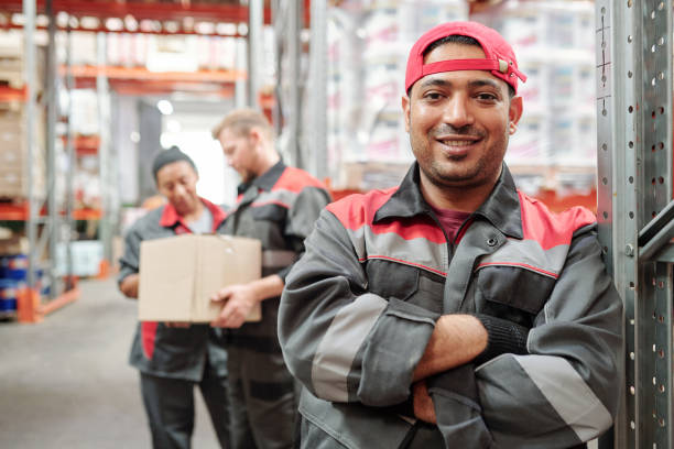 Happy young Latino man in workwear and gloves crossing arms by chest stock photo