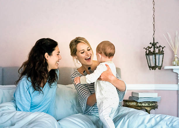 happy young lesbians playing with baby boy in bed - lesbian stock photos and pictures