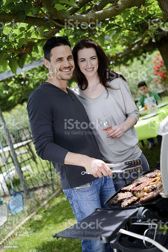 happy young loving couple cooking  together barbecue party in summertime stock photo