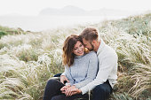 istock Happy young loving couple sitting in feather grass meadow, laughing and hugging, casual style sweater and jeans 1064352798