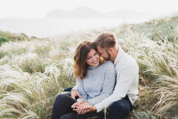 happy young loving couple sitting in feather grass meadow, laughing and hugging, casual style sweater and jeans - fidanzamento foto e immagini stock