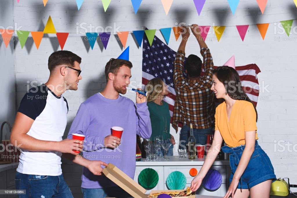 happy young male and female friends smiling each other while having fun and partying together stock photo