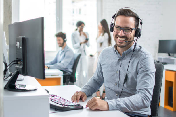 Happy young male customer support executive working in office. stock photo