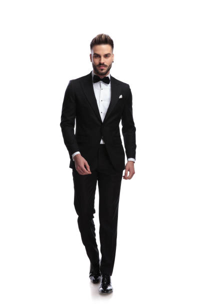 happy young male fashion model in tuxedo is walking happy young male fashion model in tuxedo is walking on white background tuxedo stock pictures, royalty-free photos & images