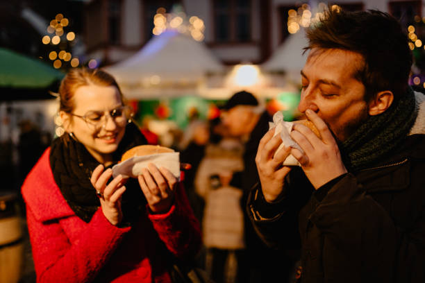 Happy young man and woman eating food on Christmas market stock photo