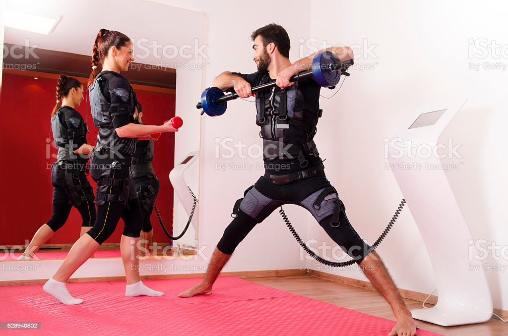 Happy young man and woman, EMS workout stock photo