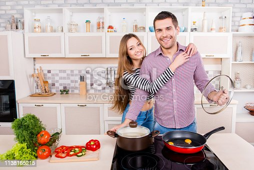 istock Happy young man and woman hugging and cooking  in the kitchen 1138165215
