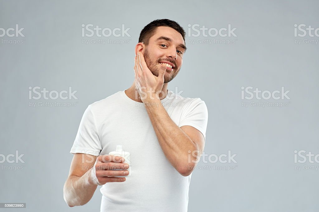 happy young man applying cream or lotion to face stock photo