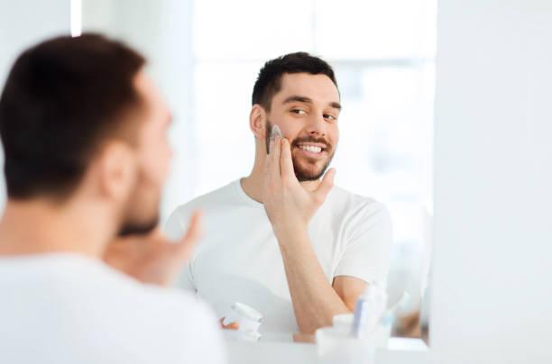 glücklicher junger Mann, der Creme auf Gesicht im Badezimmer auftragen – Foto