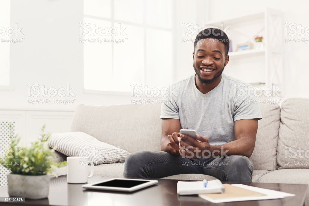 Happy young man at home messaging on mobile stock photo