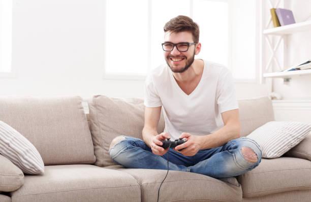 happy young man at home playing video games - man joystick imagens e fotografias de stock