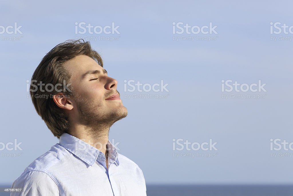 Happy young man breathing deep foto