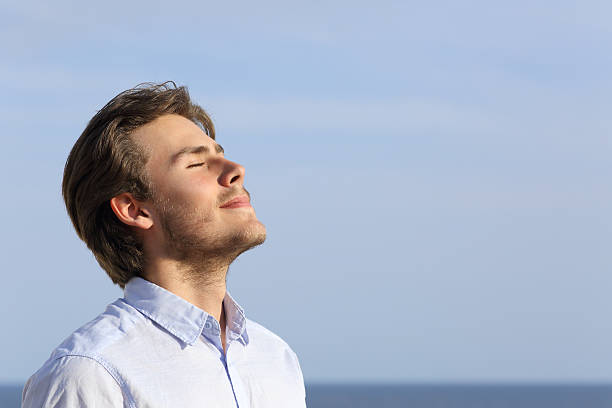 Happy young man breathing deep stock photo