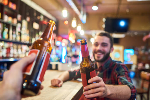 Happy young man clinking bottles with friend in bar picture id891385170?b=1&k=6&m=891385170&s=612x612&w=0&h=sn gr2shhi5tpwgs8p3o73a u2 0vvcnefblvsnb2q0=