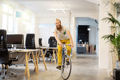 Happy young man cycling through a startup office