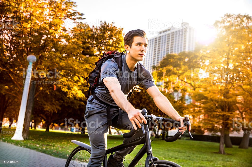 Happy young man cycling in the city, commuting to work stock photo
