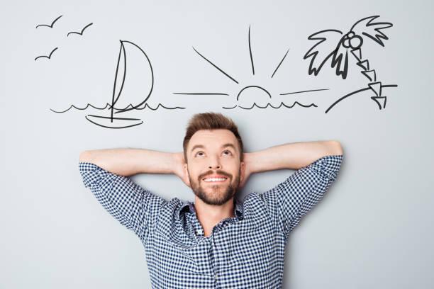休暇を夢見て幸せな若い男。海辺のオーバーヘッドの図を描画 ストックフォト