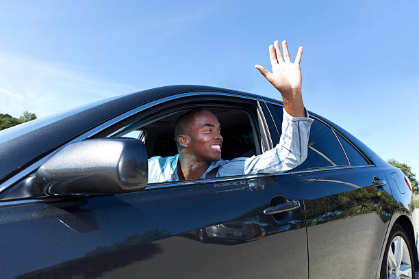 A happy young man driving and waving stock photo
