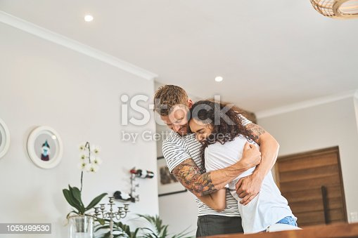 Affectionate young man embracing girlfriend in living room. Multi-ethnic couple is enjoying leisure time at home. They are in casuals.