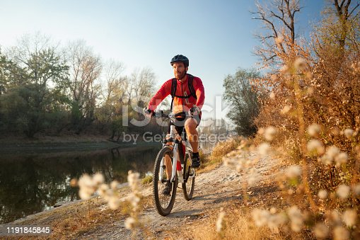 Happy young bearded man wearing red long sleeve cycling jersey and a backpack enjoying late afternoon mountain bike ride through the forest by river on a clear autumn day