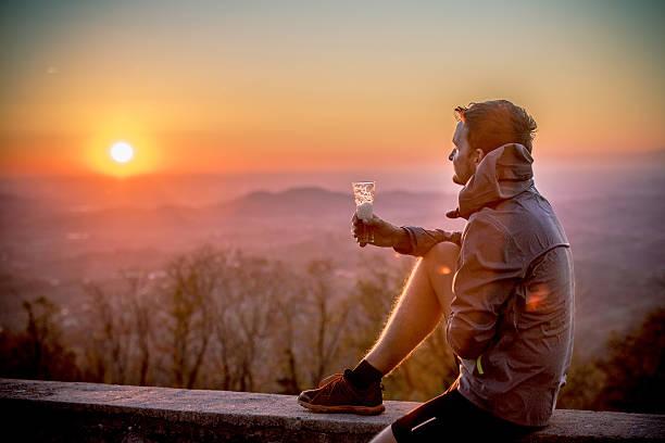 happy young man enjoying sunset after cross-country running, alps, europe - bier gesund stock-fotos und bilder