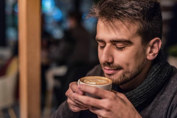 Happy young man enjoys his coffee breaks. stock photo