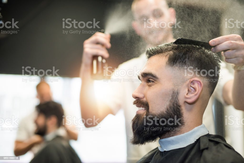 Happy young man getting a haircut. royalty-free stock photo