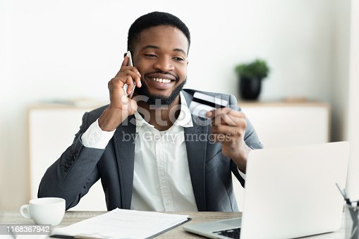 1173546354 istock photo Happy young man holding credit card and talking on cellphone 1168367942