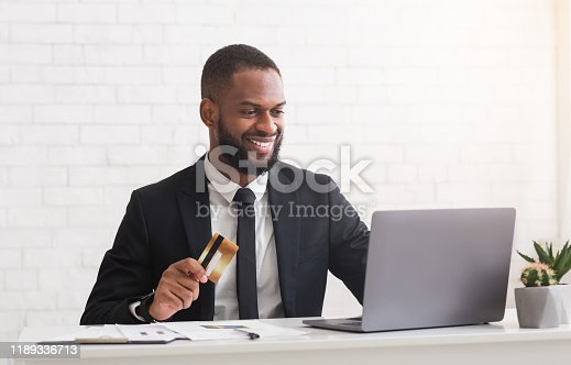 1173546354 istock photo Happy young man holding credit card, making purchases online 1189336713