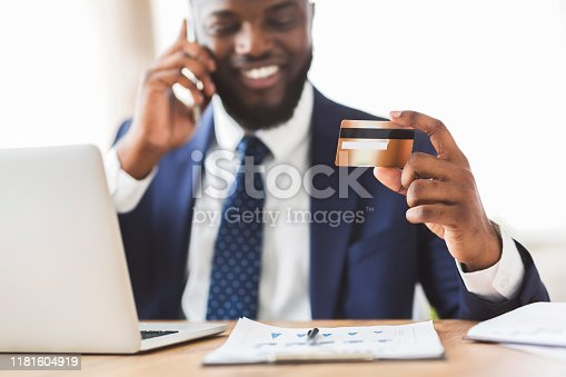 1173546354 istock photo Happy young man holding credit card, talking on phone 1181604919