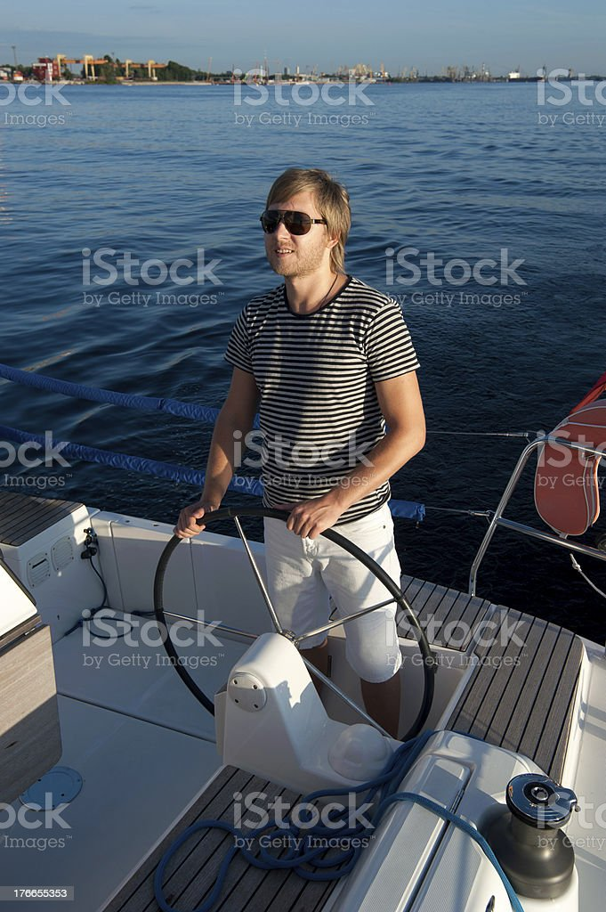 Happy young man holding steering wheel of the yacht royalty-free stock photo