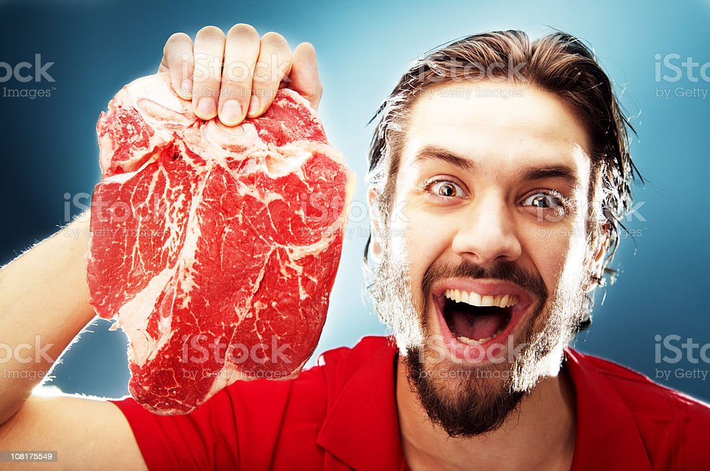 Happy Young Man Holding Up Raw Steak royalty-free stock photo