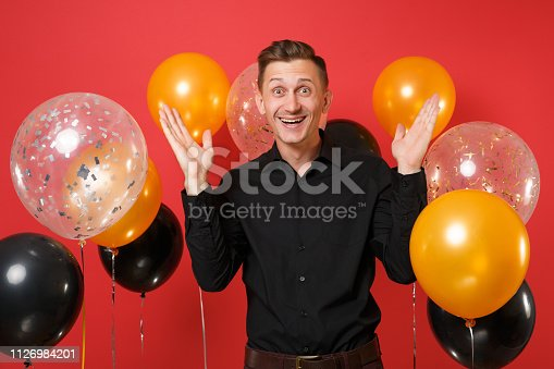istock Happy young man in black classic shirt celebrating spreading hands on bright red background air balloons. Valentine's, International Women's Day, Happy New Year, birthday mockup holiday party concept. 1126984201