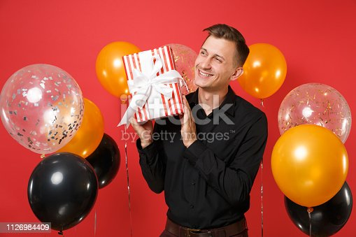 istock Happy young man in black classic shirt looking aside, holding red box with gift, present on red background air balloons. International Women's Day Happy New Year birthday mockup holiday party concept. 1126984409