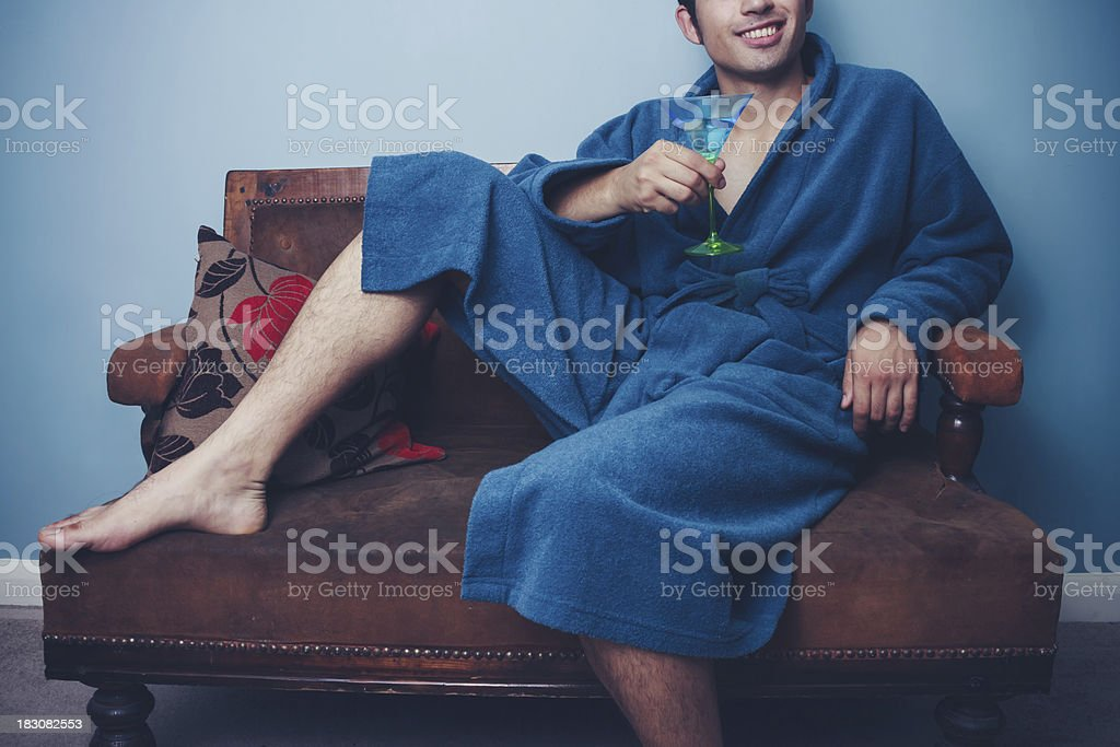 Happy young man in dressing gown drinking cocktails stock photo
