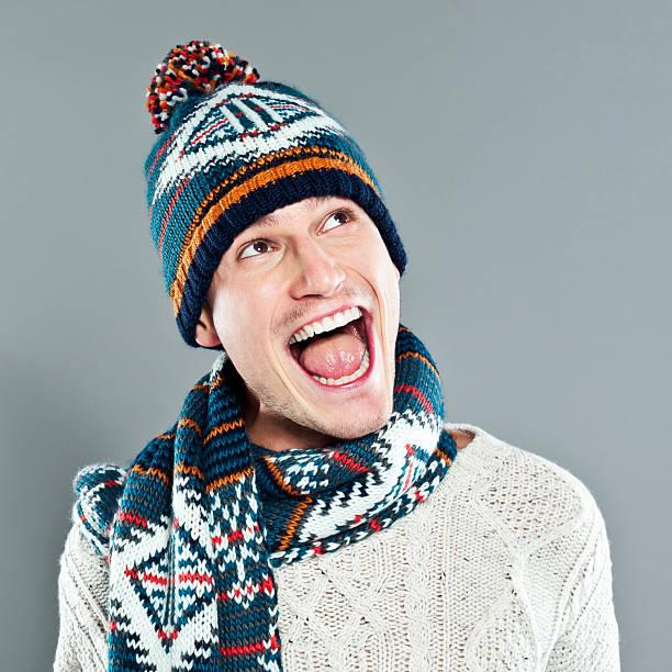 glückliche junge mann in winter-kleidung - mützenschal stock-fotos und bilder