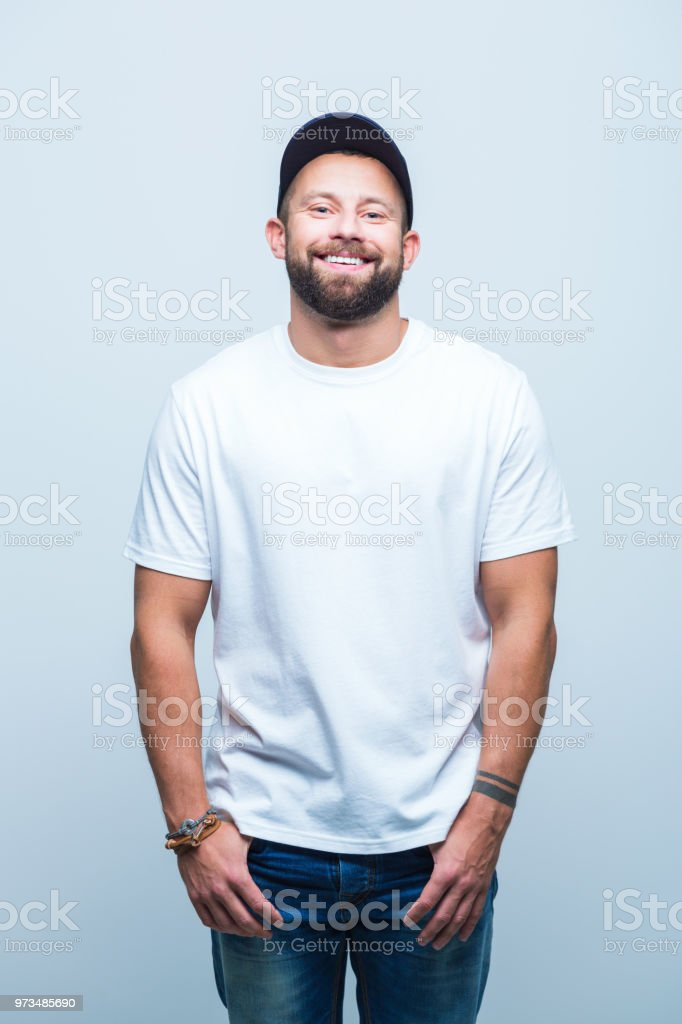 Happy young man is casuals Portrait of happy young man is casuals standing on white background with hands in pocket. Adult Stock Photo
