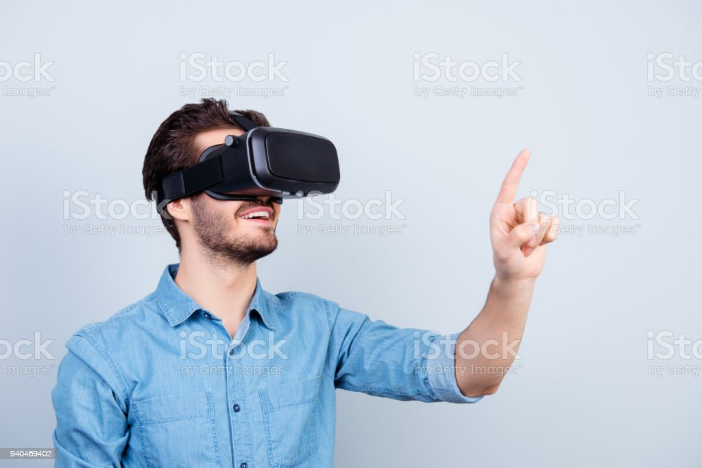 Happy young man is using vh headset glasses of virtual reality, pointing on sopmething with finger stock photo