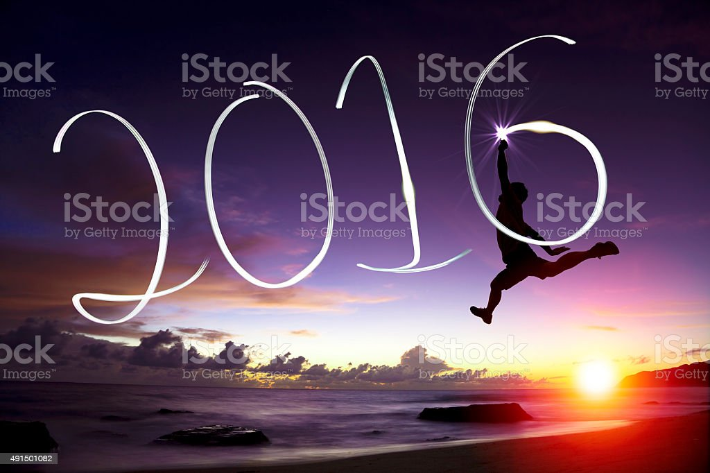 happy young man jumping  and drawing 2016 in the air stock photo
