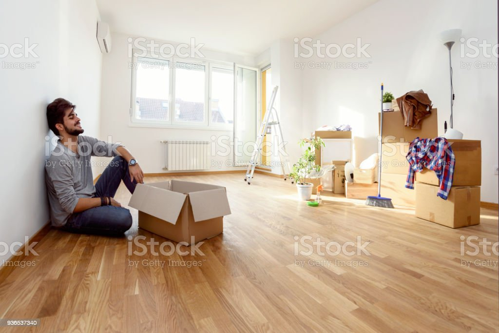 Happy young man just moved into new home unpacking boxes sitting on the floor stock photo