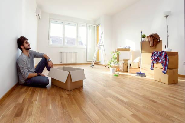 glücklicher junger mann gerade umgezogen in neue heimat auspacken der kartons auf dem boden sitzend - neue wohnung stock-fotos und bilder