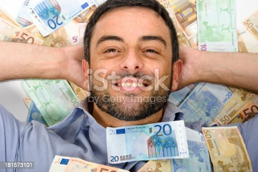 istock Happy Young Man laying on Banknotes 181573101