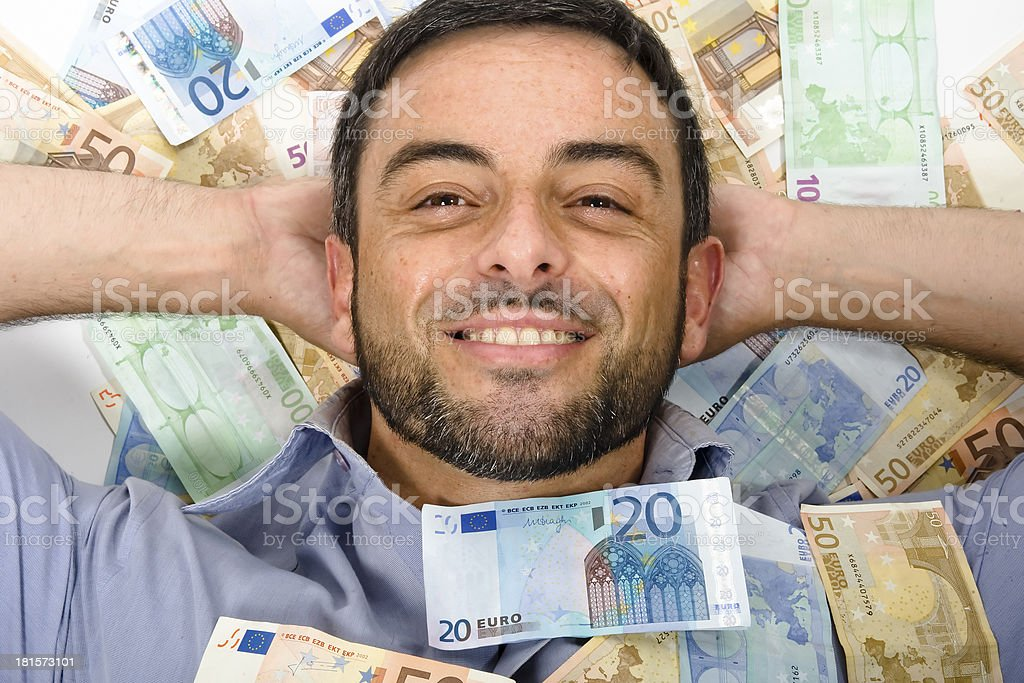 Happy Young Man laying on Banknotes stock photo