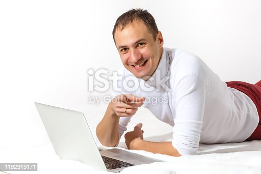 947303582 istock photo Happy young man lies on a floor and using laptop isolated over white background 1192919171