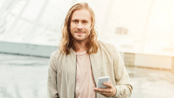 happy young man listening music with earphones and smartphone on street and looking at camera - medium length hair stock photos and pictures