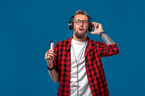 Happy young man listening to music with headphones. Handsome smiling guy in checkered shirt with closed eyes dancing with headphones. Isolated on blue background. Concept of people emotions